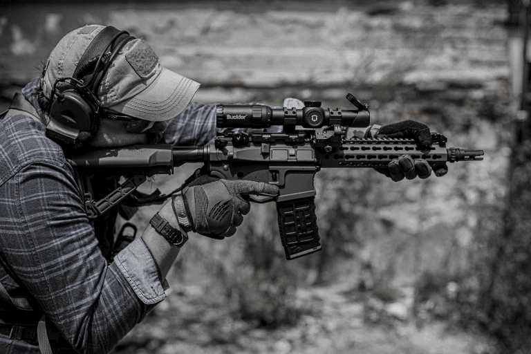 man aiming assault rifle with stock