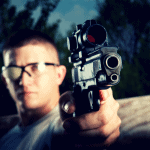 man aiming pistol with red dot sight