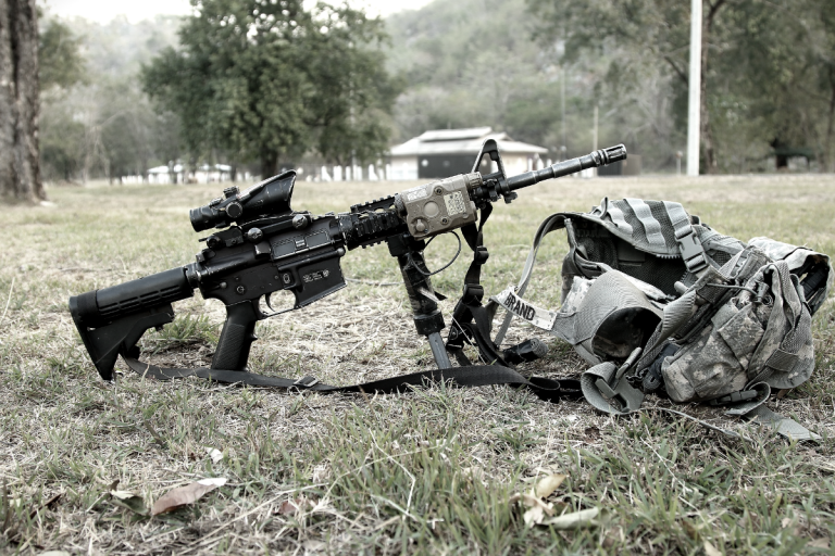army assault rifle on grass military bag