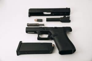 Disassembled Glock G43X (barrel, guide rod, and slide removed), loaded magazine, and 9mm round.